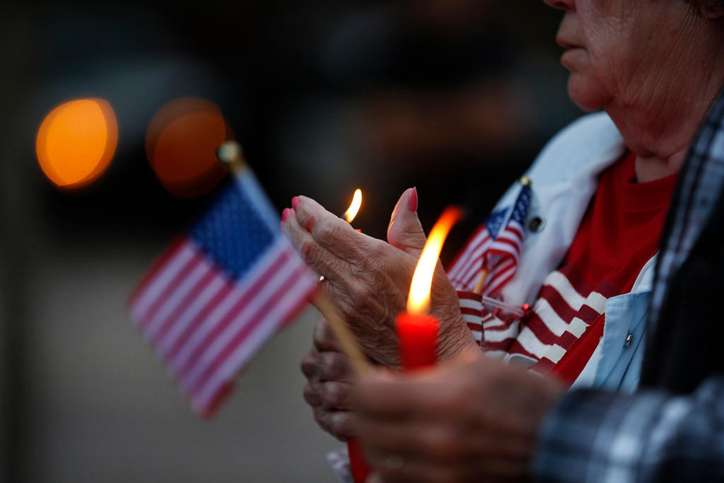 . Members of the community hold candles and American flags during a candlelight vigil for slain Hayward police Sgt. Scott Lunger at Hayward City Hall in Hayward, Calif., on Wednesday, July 22, 2015. Lunger was killed during a traffic stop early Wednesday. (Ray Chavez/Bay Area News Group)Lin