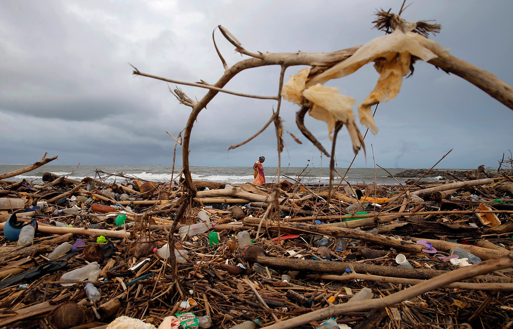 ". A Sri Lankan ragpicker searches for plastic waste washed ashore on the promenade of the Indian ocean in Colombo, Sri Lanka, Monday, June 4, 2018. This year\'s World Environment Day theme, marked on June 5, is ""Beat Plastic Pollution.\"" (AP Photo/Eranga Jayawardena)"