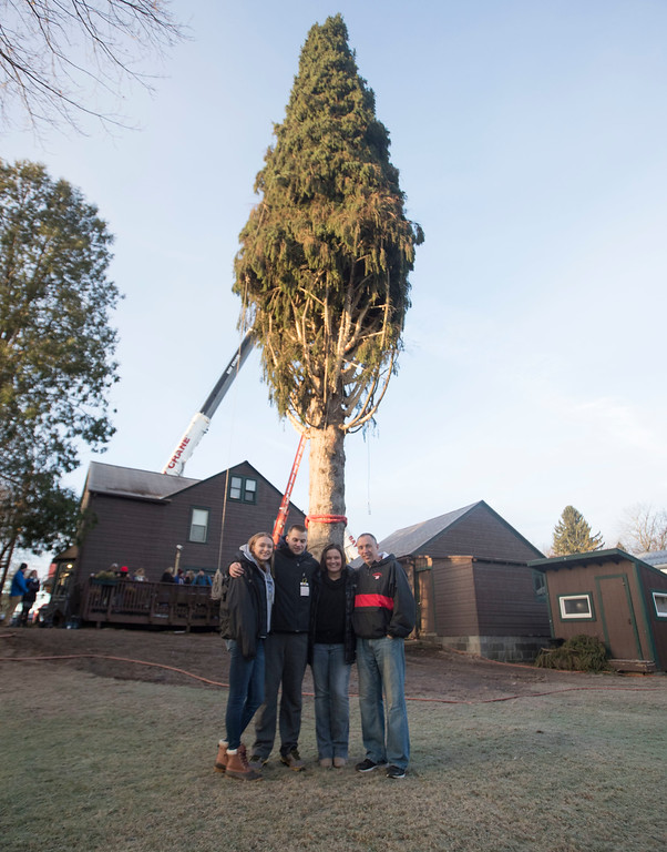 . Graig Eichler, right, his wife Angie and their children Ava and Brock pose in front of a 94-foot Norway spruce that will serve as the Christmas tree at Rockefeller Center on Thursday, Nov. 10, 2016, in Oneonta, N.Y. The spruce is due to arrive Saturday in Manhattan, about 140 miles away. (AP Photo/Mike Groll)