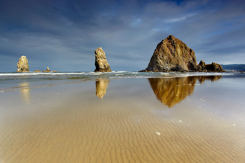 Canon Beach in Northern Oregon is an exceptionally wide, long and flat beach with a number of large rock islands and sea stacks offshore.  Low tide is often the best time to see it because you can get closer to the rocks and the sand is glossy and smooth both for walking and for photography.  On this morning, a small hole opened up in the clouds deck and for two short minutes, the sun illuminated this scene against a dark sky.  I had already moved into a good position with the ripples pointing towards the middle stack.  After that, I hoped for some nice  light!