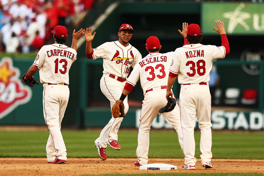 . ST LOUIS, MO - OCTOBER 12:  Matt Carpenter #13, Jon Jay #19, Daniel Descalso #33 and Pete Kozma #38 of the St. Louis Cardinals celebrate their 1 to 0 win over the Los Angeles Dodgers  during Game Two of the National League Championship Series at Busch Stadium on October 12, 2013 in St Louis, Missouri.  (Photo by Elsa/Getty Images)