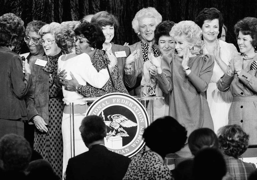 . First Lady Nancy Reagan left, is hugged by singer Pearl Bailey as, from left, Carla Hills, Barbara Bush, U. S. Treasurer Katherine Ortega and Joan Rivers applaud during a reception in Dallas on Wednesday, August 22, 1984. (AP Photo/Lana Harris)