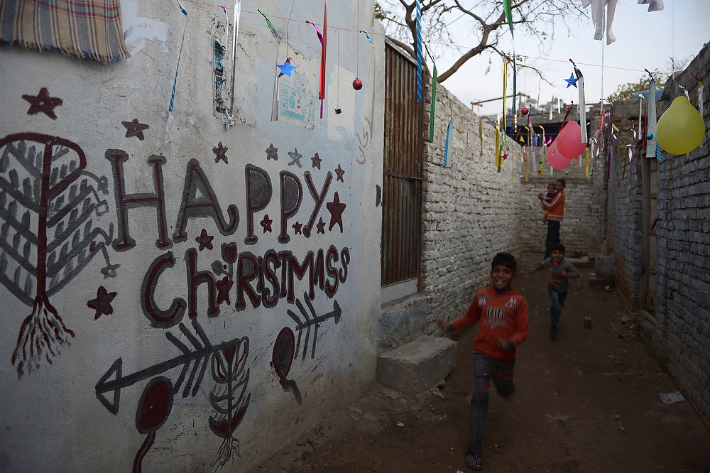 Description of . Minority Pakistani Christians walk in an alley past Christmas decorations in Islamabad on December 24, 2012. There is a tiny Christian minority in Pakistan, where only three percent of the population of 167 million are estimated to be non-Muslim. FAROOQ NAEEM/AFP/Getty Images