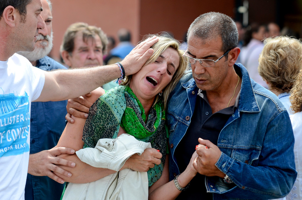 . Relatives of victims involved in a train accident react at a victims information point in Santiago de Compostela, Spain, on Thursday July 25, 2013. Relatives of victims from a train crash in northwestern Spain sobbed and hugged each other Thursday near a makeshift morgue in a sports arena for the victims as the death toll rose to 78 and investigators tried to determine the cause. The train jumped the tracks and at least one passenger told a radio station that it appeared to be going very fast as it went into a pronounced curve while approaching the station in this Catholic shrine city on the eve of a major religious festival. (AP Photo/Brais Lorenzo)