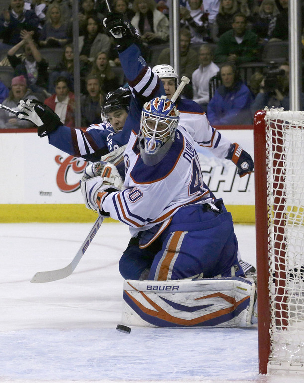 . Edmonton Oilers goalie Devan Dubnyk (40) watches the puck after Colorado Avalanche right wing P.A. Parenteau (15) scored a goal in the first period of an NHL game on Friday, April 19, 2013, in Denver. (AP Photo/Joe Mahoney)