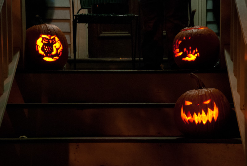 Jack O'Lanterns hang out on a porch in Brookline.