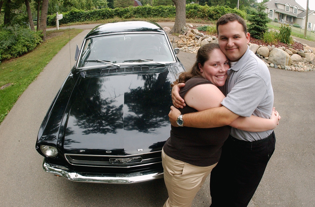 . Michelle Barnett, left, hugs her fiance, Bryan Crandall, in front of Bryan\'s father\'s 1966 Mustang, which they will drive after their wedding on Saturday, along the Dream Cruise route.  Photo taken on Thursday, August 18, 2005, in Waterford, Mich.