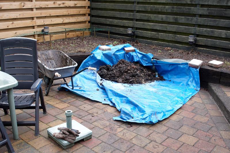 De grond die uit het gat komt wordt voorlopig op een stuk zeil gelegd