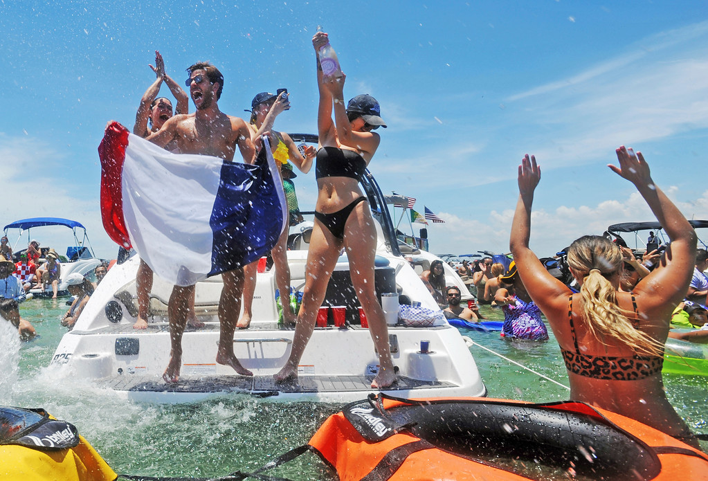 ". France team fan Kevin Ducros, left, celebrates alongside friends while attending the""Ballyhoo Boat Bash\"" that attracted fans to a water-based World Cup watch party in Miami, Sunday, July 15, 2018. The final game was streamed  at Haulover Sandbar as attendees watched France\'s second World Cup title in Moscow, Russia. (Jim Rassol/South Florida Sun-Sentinel via AP)"