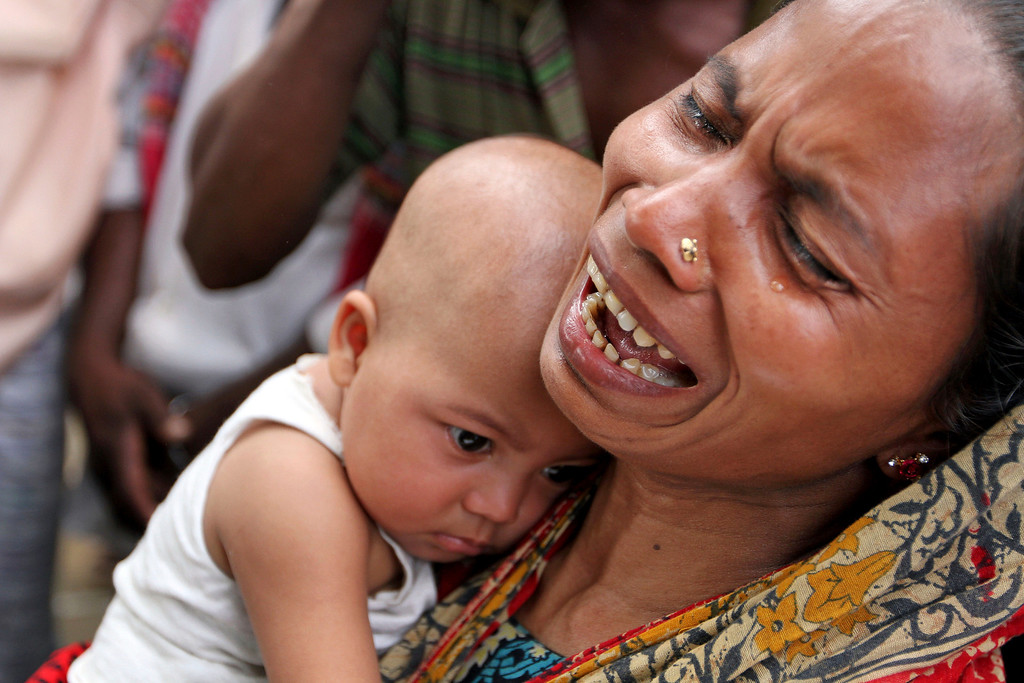 . A Bangladeshi woman holds her daughter and weeps as Bangladeshi people hold photographs of their relatives whom they believe are trapped in the rubble of a building that collapsed in Savar, outskirts of Dhaka, Bangladesh, Tuesday, April 30, 2013. (AP Photo/Palash Khan)