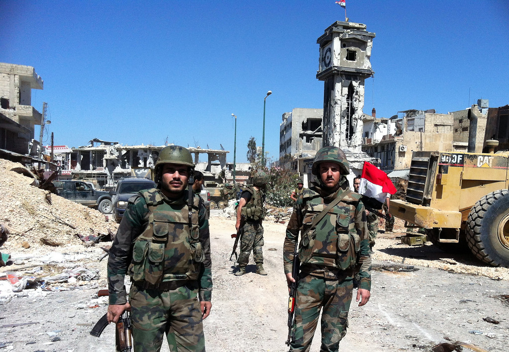 . Syrian government soldiers stand in front of the clock tower flying the national flag in the main square of the city of Qusayr, in Syria\'s central Homs province, on June 5, 2013, after the army claimed it had seized total control of it and the surrounding region. Syria\'s rebels conceded they had lost the battle for the strategic town of Qusayr which was vital for the opposition as it was their principal transit point for weapons and fighters from neighbouring Lebanon.  AFP PHOTO / STRSTR/AFP/Getty Images