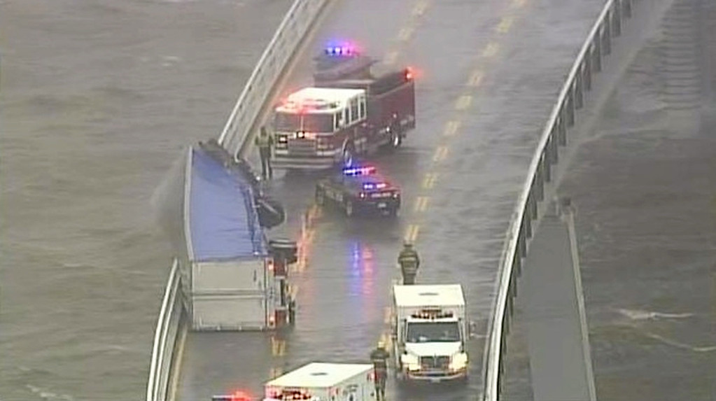. In this image from video provided by WJZ-TV, emergency crews surround a tractor-trailer that overturned on the westbound span of the Bay Bridge, which crosses the Chesapeake Bay in Maryland. The bridge was closed in both directions after the crash Wednesday afternoon due to high winds from a snowstorm blowing through the Mid-Atlantic region. (AP Photo/WJZ-TV)