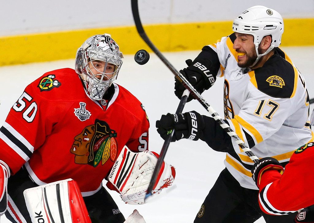 . Boston Bruins\' Milan Lucic (R) battles for the rebound with Chicago Blackhawks goalie Corey Crawford during the third period in Game 5 of their NHL Stanley Cup Finals hockey series in Chicago, Illinois, June 22, 2013. REUTERS/Jeff Haynes