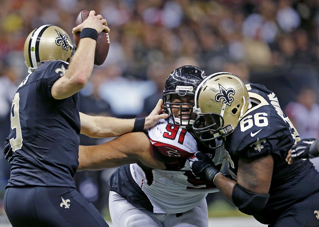 . New Orleans Saints quarterback Drew Brees (9) tries to avoid the pass rush of Atlanta Falcons defensive tackle Corey Peters (91) as guard Ben Grubbs (66) defends in the second half of an NFL football game in New Orleans, Sunday, Dec. 21, 2014. (AP Photo/Bill Haber)