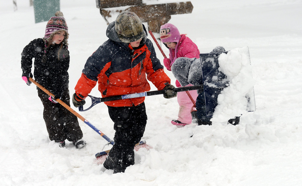 . Wear appropriate outdoor clothing: a tightly woven, preferably wind-resistant coat or jacket; inner layers of light, warm clothing; mittens; hats; scarves; and waterproof boots. Pictured here, Dominic Pandolfi and friends Emma Fitzpatrick, left, and her sister Chloe help shovel the driveway of the Galon family on Weatherby Drive in Mentor in February 2014. (News-Herald file)