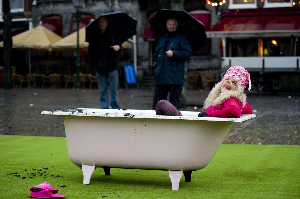Description of . A woman disguised as muppet character Miss Piggy takes a mud bath in front of the House of Representatives in The Hague on December 1, 2011 during a protest with Dutch environmental organization Milieudefensie against the expansion of livestock farming. AFP PHOTO / ANP ROBIN UTRECHT