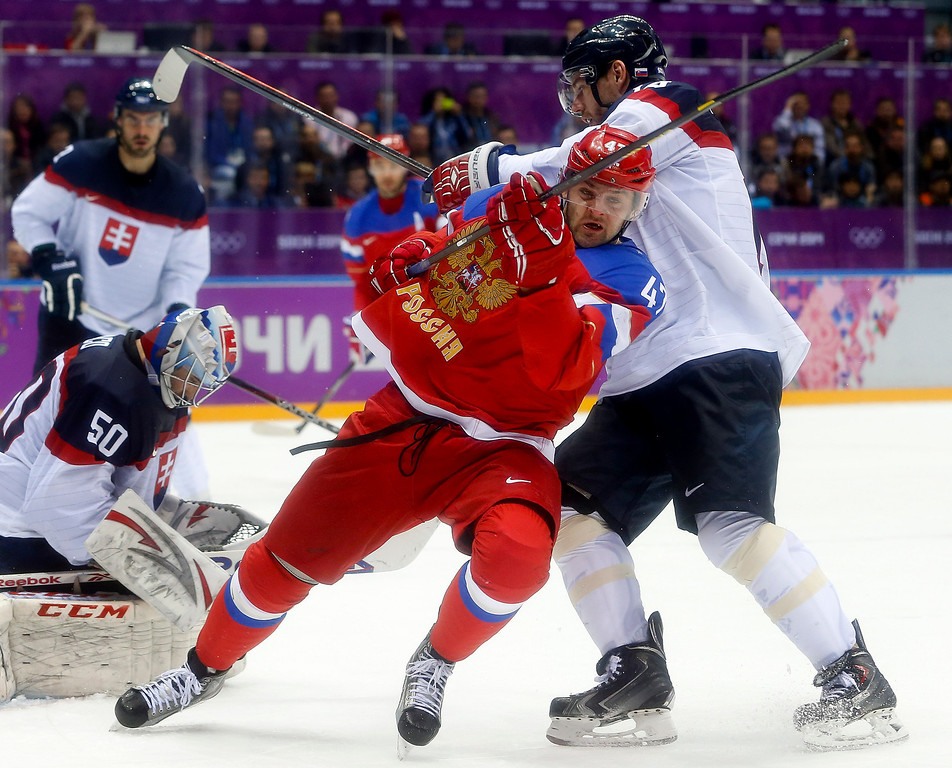 . Russia forward Alexander Radulov gets tangled up with Slovakia defenseman Andrej Meszaros in the third period of a men\'s ice hockey game at the 2014 Winter Olympics, Sunday, Feb. 16, 2014, in Sochi, Russia. (AP Photo/Mark Humphrey)