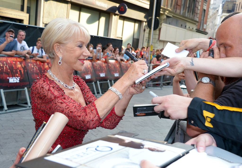 . Dame Helen Mirren signs autographs as she arrives at the European Premiere of Red 2, on Monday July 22, 2013 in London. (Photo by Jon Furniss/Invision/AP Images)