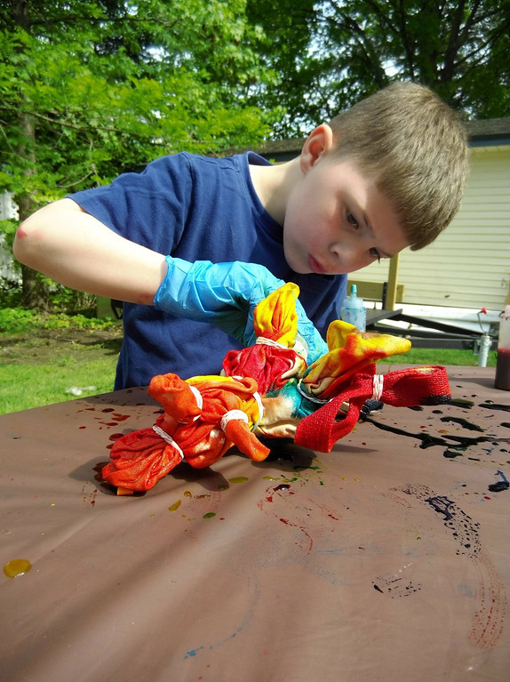 . Colsen Swinehart adds another splash of color to his tie-dye bag during a crafty program at Mentor Public Library. (Courtesy Mentor Public Library)