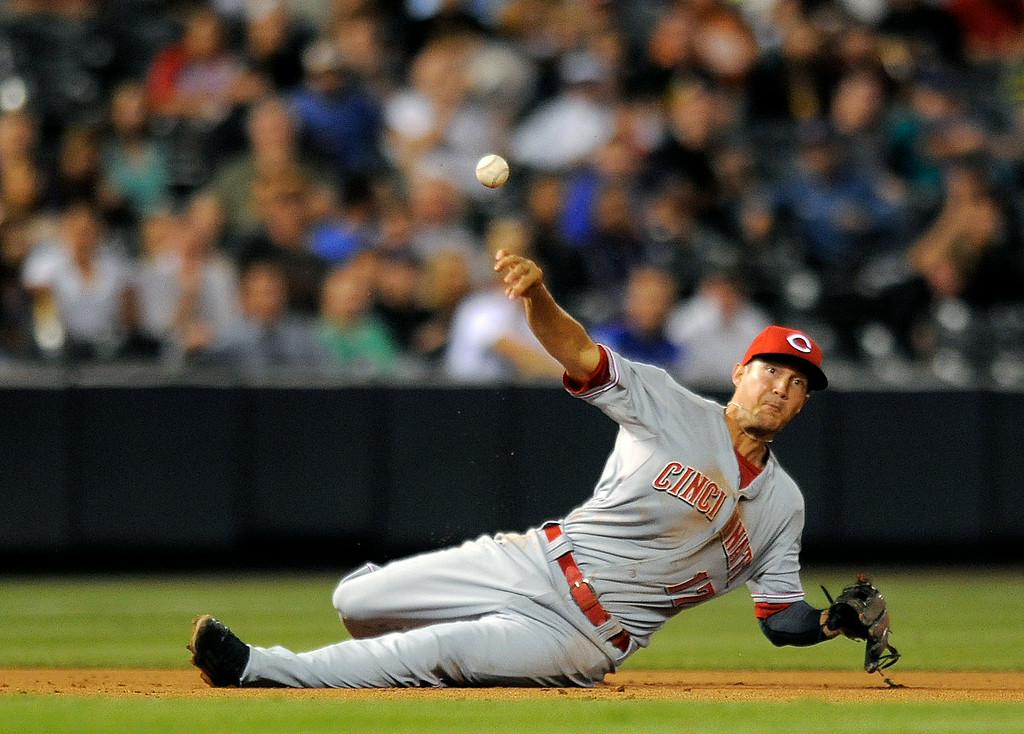 . Cincinnati Reds third baseman Kris Negron throws to first base from the ground on a single by Colorado Rockies Nolan Arenado in the fifth inning of a baseball game on Thursday, Aug. 14, 2014, in Denver. (AP Photo/Chris Schneider)