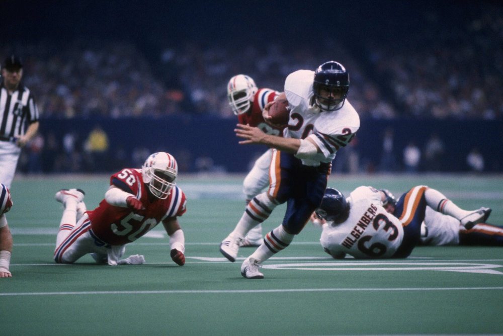 Description of . 26 Jan 1986: Running back Matt Suhey #20 of the Chicago Bears breaks through the defense of the New England Patriots and scores the first touchdown by the Bears in Superbowl XX at the Louisiana Superdome in New Orleans, Louisiana. The Bears defeated the Patriots 46-10.
