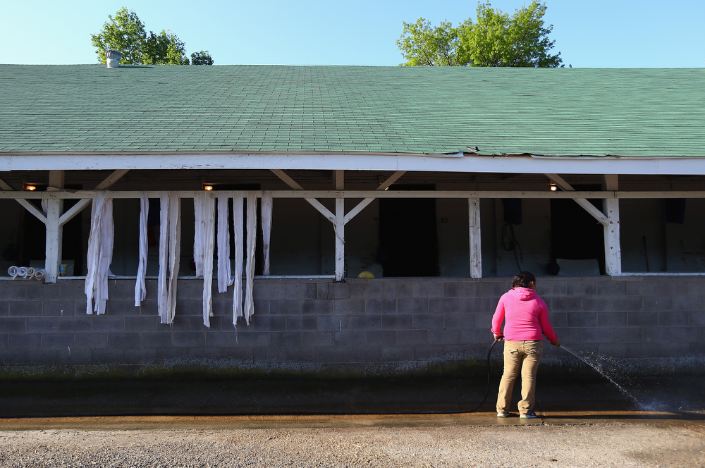 . A barn worker cleans the outside of a barn during the morning training for the Kentucky Derby at Churchill Downs on May 1, 2014 in Louisville, Kentucky.  (Photo by Andy Lyons/Getty Images)
