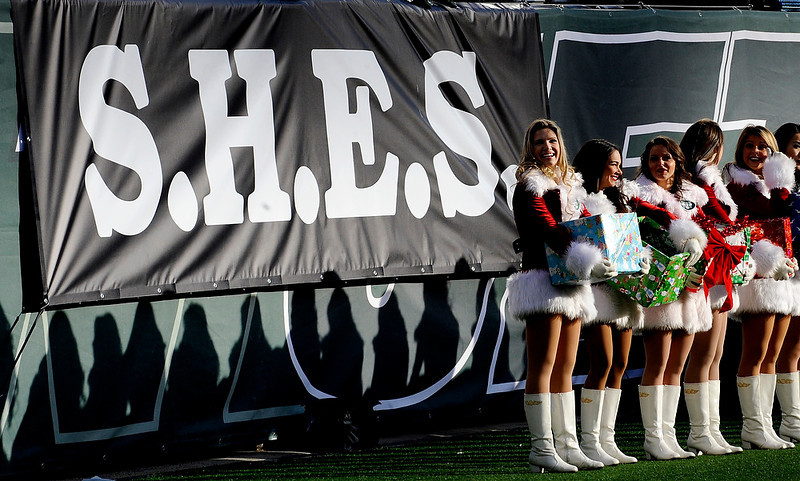 . New York Jets cheerleaders stand near a banner in memory of the victims of the Sandy Hook Elementary School shooting in Newtown, Conn., during the first half of an NFL football game between the New York Jets and the San Diego Chargers, Sunday, Dec. 23, 2012, in East Rutherford, N.J. (AP Photo/Bill Kostroun)