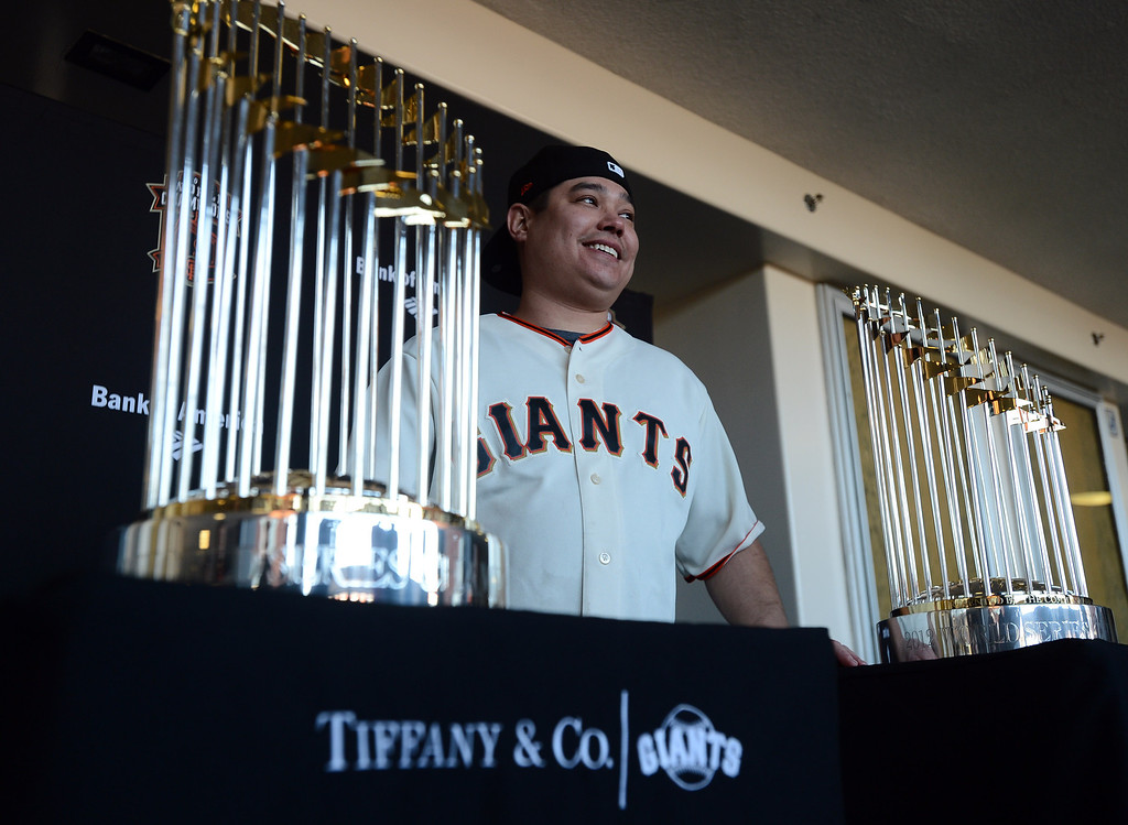 . Craig Takehara, of Sacramento, smiles as he is photographed with the World Series Trophy as it makes a stop at the Richmond Memorial Auditorium in Richmond, Calif. on Monday, Jan. 14, 2013.  (Kristopher Skinner/Staff)