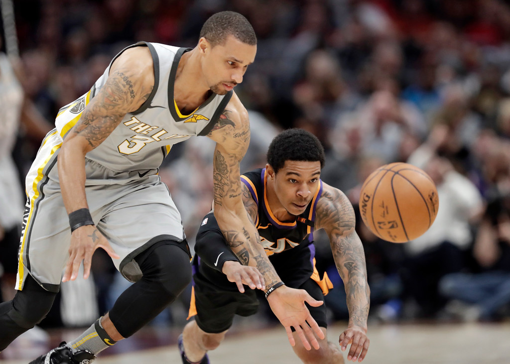 . Cleveland Cavaliers\' George Hill, left, and Phoenix Suns\' Tyler Ulis eye the ball during the first half of an NBA basketball game Friday, March 23, 2018, in Cleveland. (AP Photo/Tony Dejak)