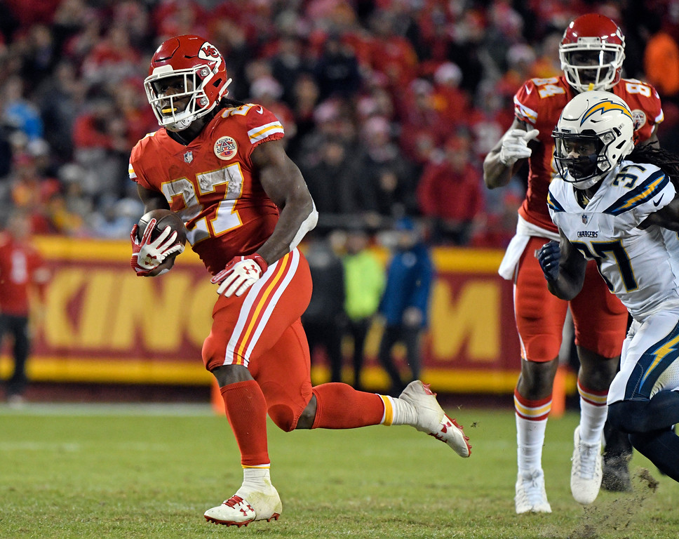 . Kansas City Chiefs running back Kareem Hunt (27) runs away from Los Angeles Chargers safety Jahleel Addae (37) during the second half of an NFL football game in Kansas City, Mo., Saturday, Dec. 16, 2017. (AP Photo/Ed Zurga)