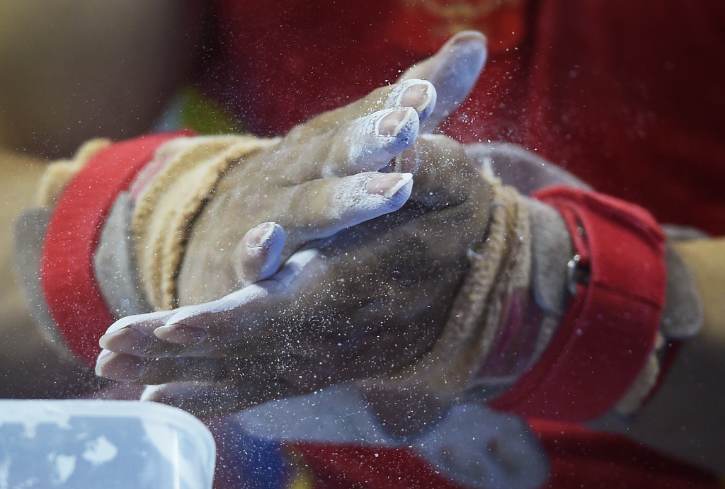 . China\'s Liu Yang rubs powder into his hands before performing on the rings during the men\'s qualification at the Gymnastics World Championships in Nanning, in China\'s southern Guangxi province on October 3, 2014. GREG BAKER/AFP/Getty Images