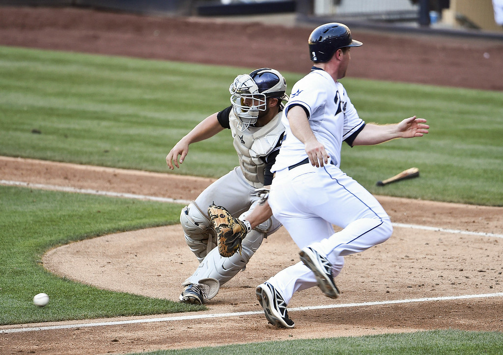 . SAN DIEGO, CA - AUGUST 13:  Jedd Gyorko #9 of the San Diego Padres scores ahead of the throw to Michael McKenry #8 of the Colorado Rockies during the fifth inning of a baseball game at Petco Park on August 13, 2014 in San Diego, California.  (Photo by Denis Poroy/Getty Images)
