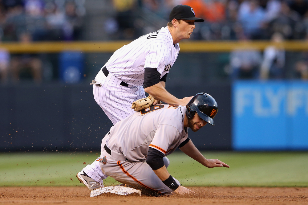 . Second baseman DJ LeMahieu #9 of the Colorado Rockies and Brandon Belt #9 of the San Francisco Giants collide after Belt was caught in a force out on a ground ball by Joaquin Arias #13 of the San Francisco Giants in the second inning at Coors Field on April 22, 2014 in Denver, Colorado.  (Photo by Doug Pensinger/Getty Images)