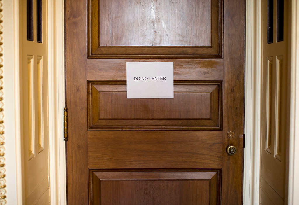 . A sign hangs on the door of the room where a Senate Democratic caucus is taking place about the ongoing budget fight, Monday, Sept. 30, 2013, on Capitol Hill in Washington.   (AP Photo/ Evan Vucci)