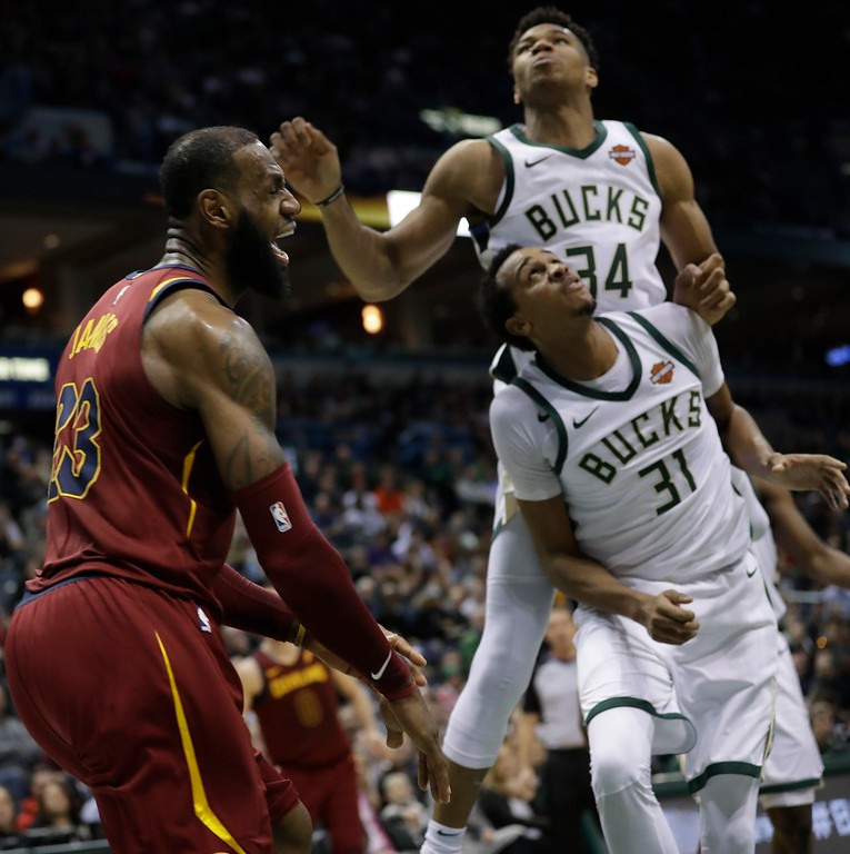 . Cleveland Cavaliers\' LeBron James reacts after making a shot in front of Milwaukee Bucks\' Giannis Antetokounmpo (34) and John Henson (31) during the first half of an NBA basketball game Tuesday, Dec. 19, 2017, in Milwaukee. (AP Photo/Morry Gash)