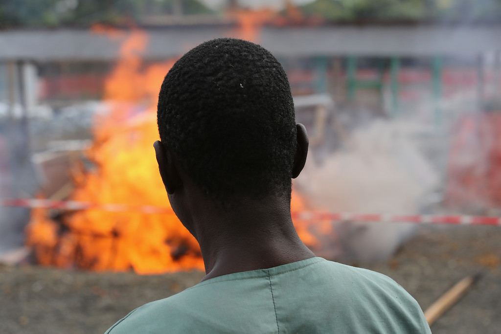 . Ebola survivor Jessy Amos, (45), and now an employee of Doctors Without Borders (MSF), watches after lighting fire to part of the Ebola Treatment Unit (ETU), on January 26, 2015 in Paynesville, Liberia. MSF, which was one of the first aid organizations to respond to the Ebola epidemic in Liberia, is destroying much of the ELWA 3 high-risk treatment area, reducing from 250 to 30 beds, in light of recent gains in eradicating the disease. In addition, other aid organizations have built ETUs, creating excess bed-space for Ebola victims around the capital of Monrovia.  (Photo by John Moore/Getty Images)