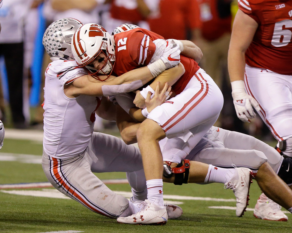 . Wisconsin quarterback Alex Hornibrook (12) is sacked by Ohio State\'s Sam Hubbard during the second half of the Big Ten championship NCAA college football game, Saturday, Dec. 2, 2017, in Indianapolis. (AP Photo/Michael Conroy)