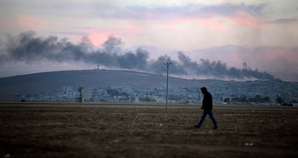 . A Turkish Kurd walks at Mursitpinar on the outskirts of Suruc, at the Turkey-Syria border, as smoke from a fire caused by a strike rises over Kobani, inside Syria, as fighting intensifies between Syrian Kurds and the militants of Islamic State group, Wednesday, Oct. 8, 2014. Kobani, also known as Ayn Arab and its surrounding areas have been under attack since mid-September, with militants capturing dozens of nearby Kurdish villages. (AP Photo/Lefteris Pitarakis)