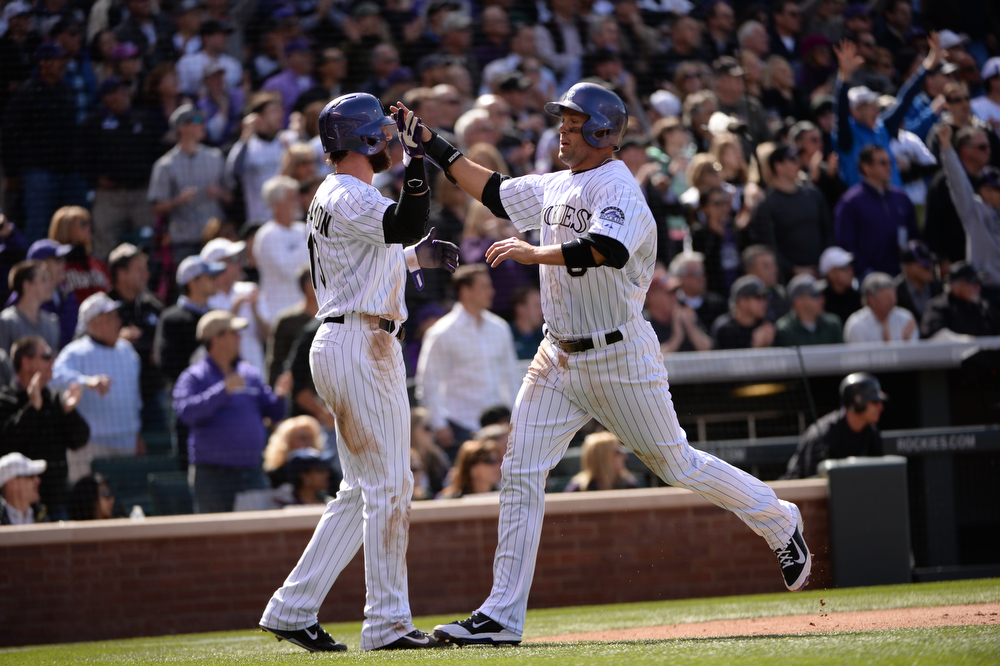 . Michael Cuddyer high-fives Charlie Blackmon after scoring on a triple by Carlos Gonzalez during the third inning. The Colorado Rockies hosted the Arizona Diamondbacks in the Rockies season home opener at Coors Field in Denver, Colorado Friday, April 4, 2014. (Photo by Hyoung Chang/The Denver Post)