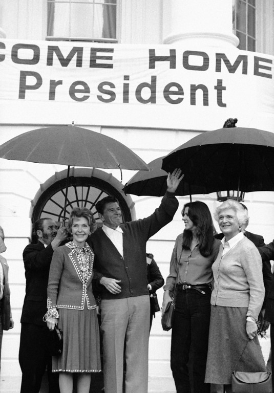 . President Ronald Reagan and Mrs.Nancy  Reagan acknowledge the crowd upon arrival at the White House in Washington  Saturday, April 11, 1981. Above them is a banner saying �Welcome Home Mr. President.� At right are their youngest daughter, Patti, and Mrs. Barbara Bush, wife of the Vice President George H.W. Bush.  (AP Photo)