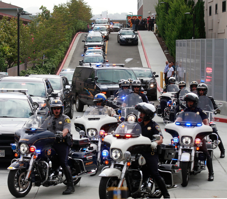 . The Alameda County Coroner is escorted by Hayward Police and California Highway Patrol as the van leaves  Eden Medical Center in Castro Valley, Calif., with the body of Hayward police Sgt. Scott Lunger on Wednesday, July 22, 2015.  (Laura A. Oda/Bay Area News Group)