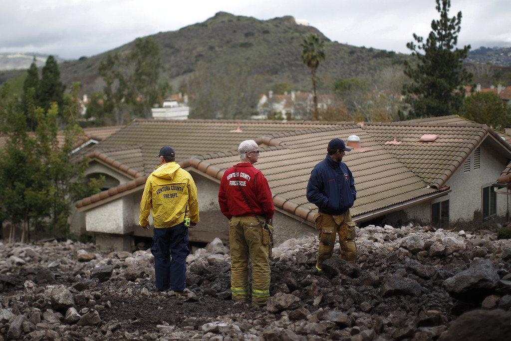 . Ventura County firefighters stand on a pile of rocks and mud after debris flows smashed into homes as a powerful storm that has been lashing northern California moves southward on December 12, 2014 in Camarillo Springs neighborhood of Camarilla, California.   (Photo by David McNew/Getty Images)