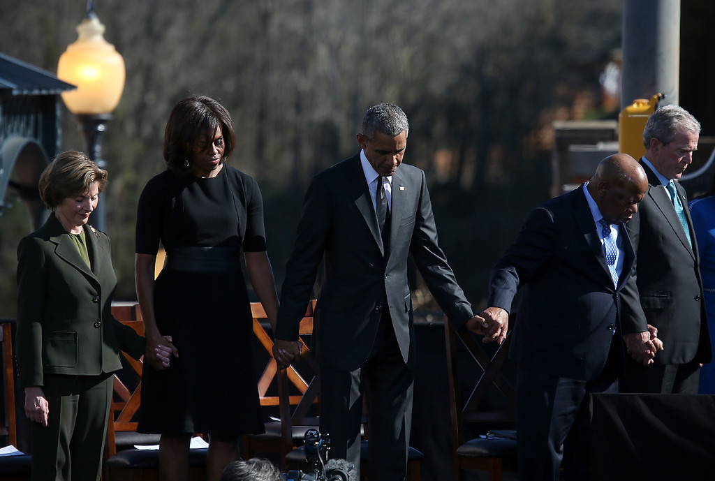 . (L-R) Former first lady Laura Bush, first lady Michelle Obama, U.S. president Barack Obama, U.S. Rep John Lewis (D-GA) and former U.S. president George W. Bush pray during a commemoration of the 50th anniversary of the historic civil rights march on March 7, 2015 in Selma, Alabama. Selma is commemorating the 50th anniversary of the famed civil rights march from Selma to Montgomery that resulted in a violent confrontation with Selma police and State Troopers on the Edmund Pettus Bridge on March 7, 1965.  (Photo by Justin Sullivan/Getty Images)