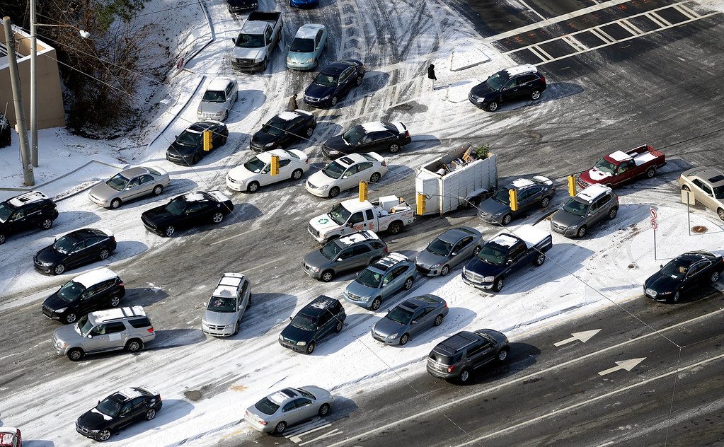 . In this view looking at Cobb Parkway at I-285, abandoned cars are piled up on the median of the ice-covered road after a winter snow storm slammed the city with over 2 inches of snow that turned highways into parking lots creating massive traffic jams lasting through Wednesday, Jan. 29, 2014, in Atlanta. (AP Photo/David Tulis)