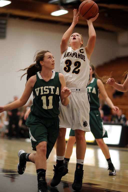 . Arapahoe\'s Mikalah Huges (32), right, scores over Mountain Vista\'s Paige Keller (11) in the first half of the game at Arapahoe High School Gym onSaturday, Jan. 5, 2013, in Centennial, Colo. Arapahoe won 74-38. Hyoung Chang, The Denver Post