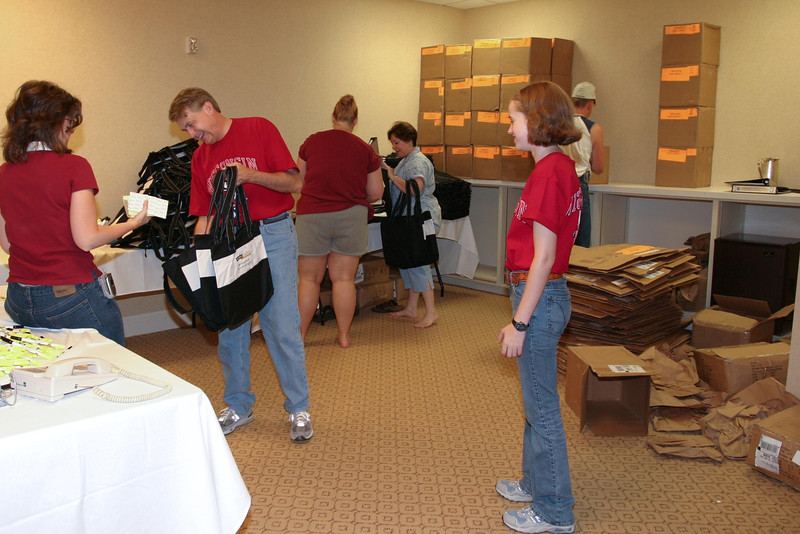 Katie Gesbeck (on the right) waiting her turn to help while her dad, Howard, fills bags at the 2004 Annual Las Vegas Conference.