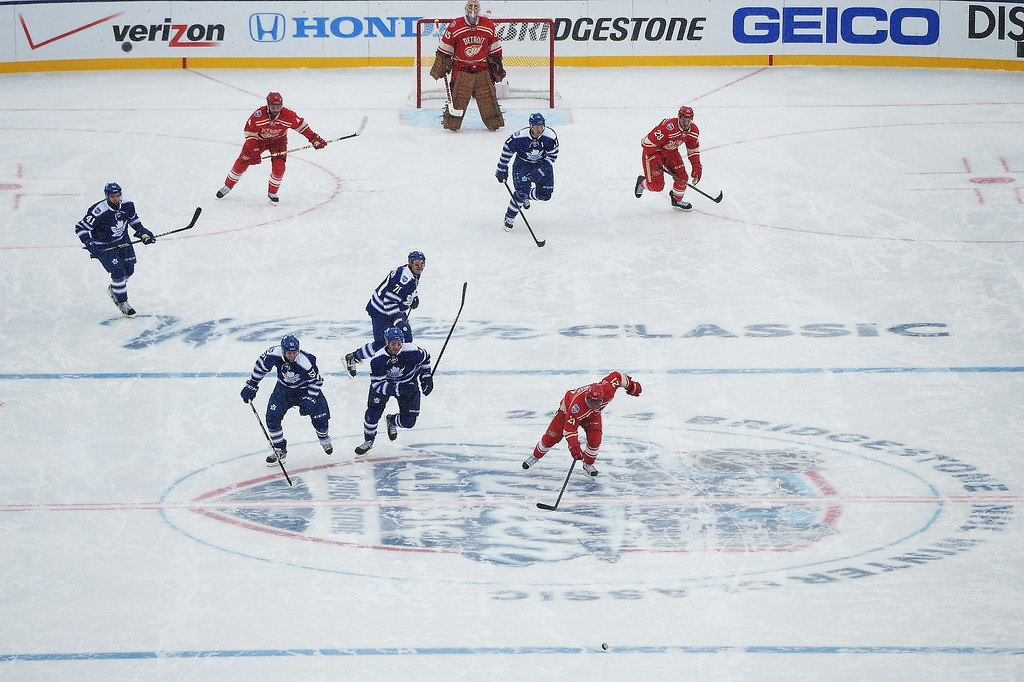 . The Toronto Maple Leafs and the Detroit Red Wings chase the puck up the ice in the third period during the 2014 Bridgestone NHL Winter Classic on January 1, 2014 at Michigan Stadium in Ann Arbor, Michigan.  (Photo by Jamie Sabau/Getty Images)
