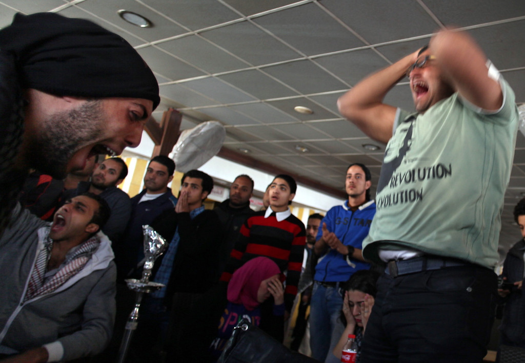 . Egyptians react after hearing a court verdict confirming death sentences against 21 people for their role in a deadly 2012 soccer riot on TV, in a coffee shop in Port Said, Egypt, Saturday, March 9, 2013. (AP Photo/Khalil Hamra)