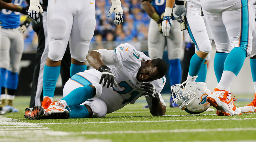 . Miami Dolphins tackle Branden Albert (71) grimaces during the first half of an NFL football game against the Detroit Lions in Detroit, Sunday, Nov. 9, 2014. Albert was carted off the field. (AP Photo/Paul Sancya)
