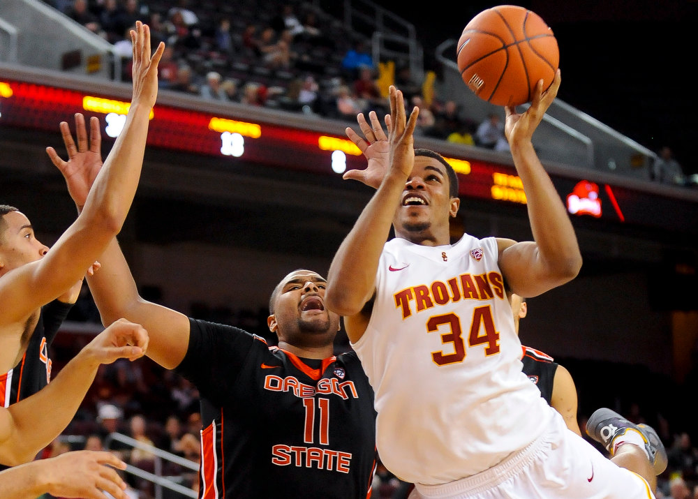 . Southern Cal forward Eric Wise (34) battles past Oregon State forward Joe Burton (11) for a basket during the second half of an NCAA college basketball game, Saturday, Jan. 19, 2013, in Los Angeles. Southern Cal won 69-68. (AP Photo/Gus Ruelas)